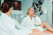 Photo selective focus of dreamy and attractive woman in bathrobe in spa