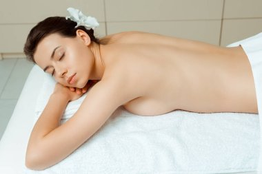 attractive woman with closed eyes and flower lying on massage table in spa
