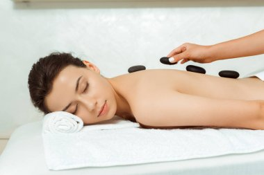 cropped view of masseur doing hot stone massage to attractive woman in spa