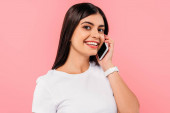 smiling pretty brunette girl talking on smartphone isolated on pink