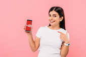 KYIV, UKRAINE - SEPTEMBER 20, 2019: smiling pretty brunette girl pointing with finger at smartphone with app isolated on pink