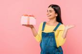 boldog terhes csinos lány gazdaság ajándék doboz elszigetelt rózsaszín