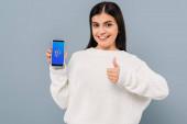 Lächelndes hübsches Mädchen im weißen Pullover zeigt Smartphone mit Shazam-App und Daumen hoch vereinzelt auf grau