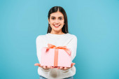 mosolygós csinos lány fehér pulóver bemutató ajándék doboz elszigetelt kék