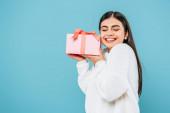 usmívající se hezká dívka v bílém svetru drží dárková krabice se zavřenýma očima izolované na modré
