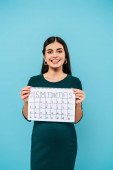 Photo smiling pregnant girl holding period calendar isolated on blue