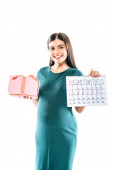 Fotografie smiling pregnant girl holding present and period calendar isolated on white