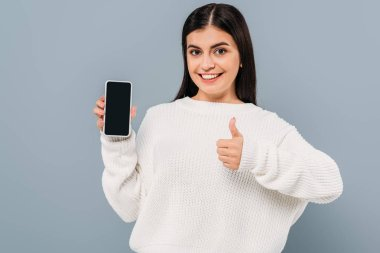 Smiling pretty girl in white sweater showing smartphone with blank screen and thumb up isolated on grey stock vector