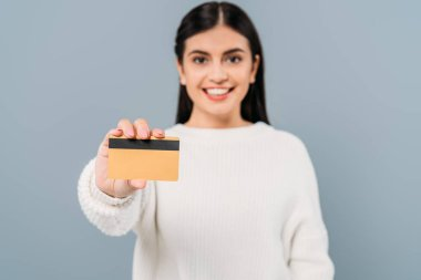 Selective focus of smiling pretty girl in white sweater presenting credit card isolated on grey stock vector