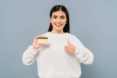 Smiling pretty girl in white sweater holding credit card and showing thumb up isolated on grey stock vector
