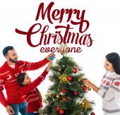 šťastná dcera zdobí vánoční stromek v blízkosti rodičů izolovaných na bílém s veselými vánocemi každý nápis