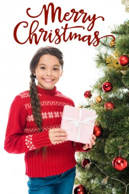 cheerful kid holding pink present near christmas tree isolated on white with merry Christmas lettering