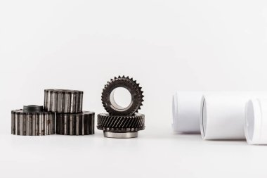 metal round gears near rolled blueprints on white background