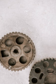 top view of aged metal round gears on grey background
