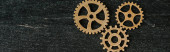 top view of vintage metal gears on dark wooden background with copy space, panoramic shot