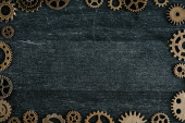 frame of vintage metal gears on dark wooden background with copy space