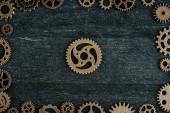 top view of vintage metal gears arranged in frame on dark wooden background