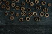 top view of vintage metal gears on dark wooden background