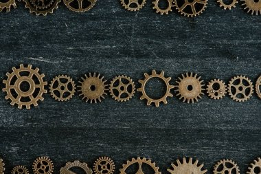 Flat lay with vintage metal gears on dark wooden background stock vector