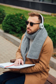 Blind man in headphones reading book with braille font in park