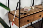 Pěší hůl vedle slunečních brýlí a knih na polici skříně
