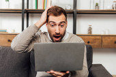 Shocked man looking at laptop on sofa in living room