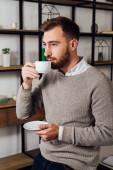 Fešák pije kávu a dívá se domů