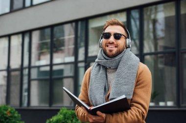 Smiling blind man in headphones holding book on urban street stock vector