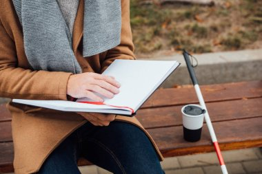 Cropped view of blind man reading book with braille font beside walking stick and thermo mug on bench