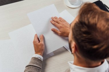 Overhead view of blind man reading braille font from paper at table