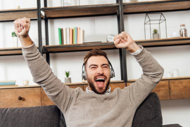 Exited man in headphones with hands in air on sofa in living room
