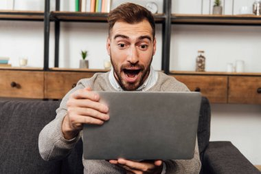Exited man holding laptop on sofa in living room