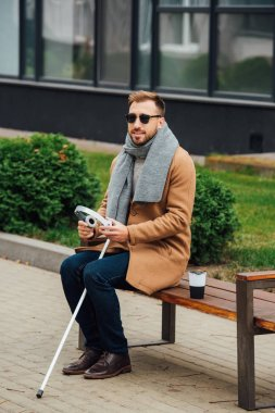Blind man holding headphones while sitting on bench