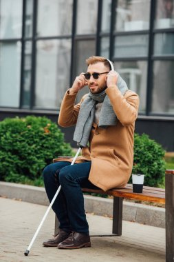 Blind man using headphones while sitting on bench