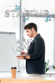 Fotografie side view of handsome in shirt using laptop in office with startup illustration