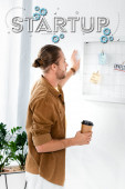 handsome man in shirt looking at white board and holding paper cup in office with startup illustration