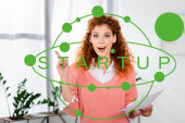 Photo attractive and shocked businesswoman showing idea sign and holding paper with startup illustration