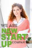 attractive and smiling businesswoman in pink sweater holding paper and pen with we are new startup company illustration