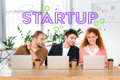 Fotografie three smiling friends sitting at table and using laptops in office with startup illustration