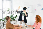 smiling businessman with vr headset gesturing in office near colleagues and startup illustration
