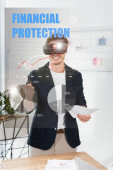 Fotografie smiling businessman in shirt with virtual reality headset holding pen and papers near financial protection illustration