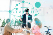 smiling businessman with vr headset in office near colleagues and startup illustration