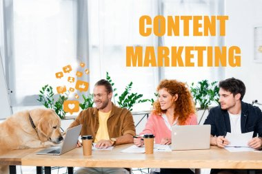 three friends smiling and looking at cute golden retriever in office with content marketing illustration