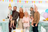 Fotografie šťastná rodina pózování na kameru, zatímco stojí v blízkosti narozeninového dortu na kuchyňském stole