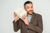 mosolygós, kíváncsi férfi rázza ajándék doboz elszigetelt szürke