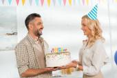 usmívající se manželka představuje narozeninový dort se šťastnými narozeninovými svíčkami na manžela