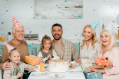 boldog család ül a konyhaasztalnál közel születésnapi torta alá esik konfetti