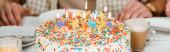 oříznutý pohled na muže sedícího u narozeninového dortu s barevnými hořícími svíčkami, panoramatický záběr
