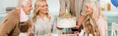 kivágott kilátás férfi gazdaság születésnapi torta gyertyákkal közel boldog család ül a konyhaasztalnál