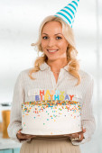 happy woman in party cap holding birthday cake with colorful candles and happy birthday lettering